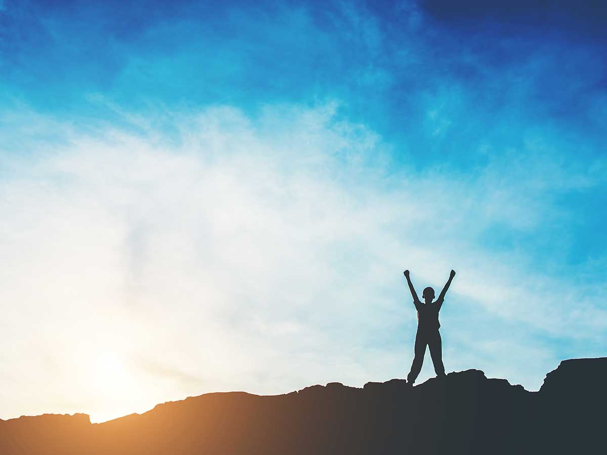 Person atop a mountain | Victory Over Sin from Share The Gift's weekly newsletter The Message